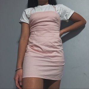 Pink gingham mini dress with lace up back.